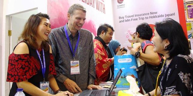 Eric Nemitz (dua kiri) berbincang dengan konsumen di booth Sompo Insurance pada acara Astindo Travel Fair 2018 di Jakarta Convention Center