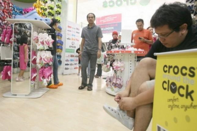 Seorang pengunjung mencoba sebuah produk baru sepatu Crocs saat acara Crocs Around The Clock di Karawaci Mall, Tangerang, Banten. (Foto: Antara)