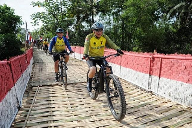 Maryono, Direktur Bank BTN, sedang bersepeda melewati salah satu jembatan pada etape BTN Tour de Borobudur 2018