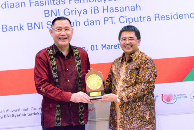 Direktur Utama BNI Syariah, Abdullah Firman Wibowo (kiri) menyerahkan cinderamata kepada Direktur PT Ciputra Residence, Mary Octo Sihombing (kanan).