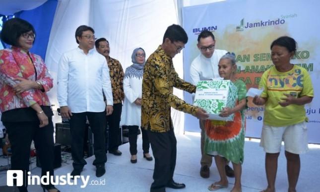 Dirut Jamkrindo Diding S Anwar (tengah), didampingi Direktur Operasional R Sohia Alizsa (kiri) membagikan paket sembako kepada warga di sekitar kantor, di Jakarta, Jumat (16/6), Kegiatan ini sebagai bagian dari program BUMN Hadir untuk Negeri. (Foto