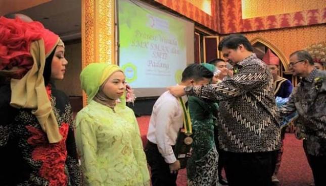 Menperin Airlangga Hartarto mengalungkan medali kepada wisudawan SMK Padang (Foto Humas)