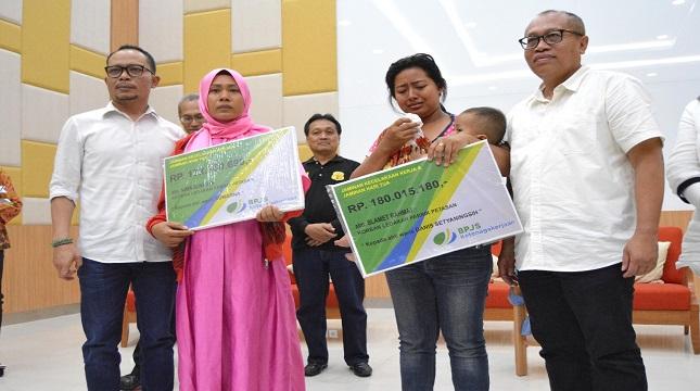 Dirut BPJS Ketenagakerjaaan Agus Susanto saat menyerahan santunan (paling kanan) (Foto;Anto/Industry.co.id).