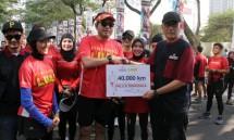 Penggagas Program LUAS IndoRunners Holil Soekawan saat menyerahkan secara simbolis total Kilometer pelari kepada Ketua Pelaksana Harian Artha Graha Peduli Heka Hertanto (Foto: Herlambang/Industry.co.id)